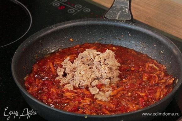 Через указанное время добавить в томатный соус кусочки тунца из банки (предварительно слив жидкость) и нарезанную зелень петрушки. Проверить соус на соль. Потушить все вместе еще минут 5 и снять с огня.