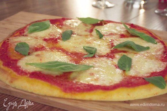 Выпекать в разогретой духовке 6–8 минут. Готовую пиццу украсить базиликом.