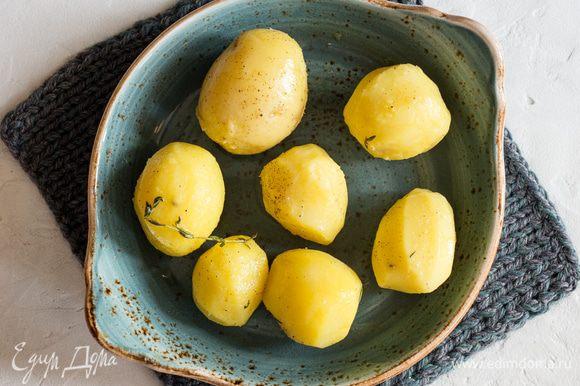 Картофель сложите на противень, сбрызните оливковым маслом, посолите, поперчите, посыпьте листочками молодого тимьяна. Перемешайте.