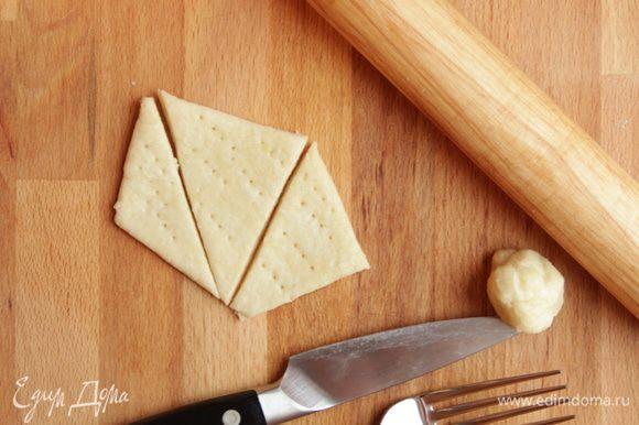 Раскатать тесто в пласт толщиной от 3 до 6 мм (по предпочтениям), нарезать геометрично, наколоть вилкой или сделать «сырные дырочки» трубочкой для напитков. Выпекать в уже разогретой до 210°С духовке.