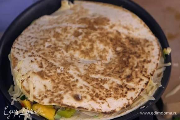 Одну тортилью прогреть на сухой сковороде, выложить на нее половину натертого сыра, фарш, маринованный перец, авокадо и соус из манго, посыпать оставшимся сыром, накрыть второй тортильей, перевернуть и прогревать все еще минуту.