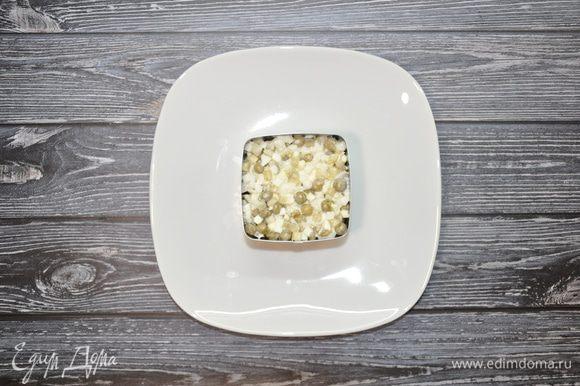 Выложите финальный слой из смеси соленых огурцов, лука, яиц и зеленого горошка.