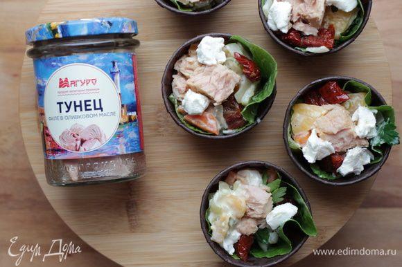На листья салата выкладываем смесь кореньев со сливками, затем брынзу кусочками, вяленые томаты и сверху выкладываем кусочки тунца. Поливаем соком с маслом из баночки. Приятного аппетита!