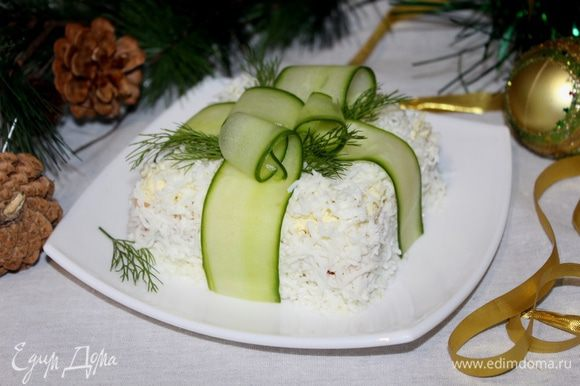 Огурец нарежьте тонкими полосками овощечисткой, «перевяжите» салат, имитируя ленту. Украсьте укропом или петрушкой.