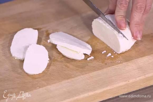 Козий сыр нарезать тонкими ломтиками.