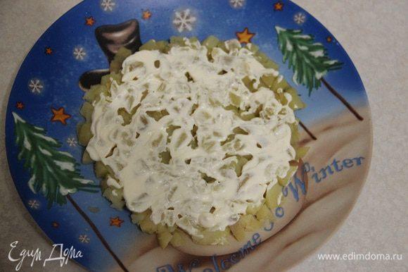Салат будем выкладывать слоями. Первый: мелко нарезанный картофель. Покроем его сверху тонким слоем майонеза ТМ «Слобода» с лимонным соком.