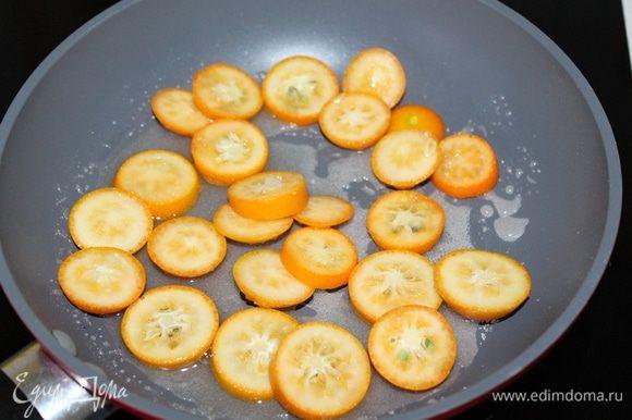 Выжать сок из апельсина, смешайте с сахаром и перелейте смесь в сковородку. Доведите до кипения. Кумкваты нарежьте на дольки, и выложите в кипящий сироп. Проварите 2 — 3 мин.