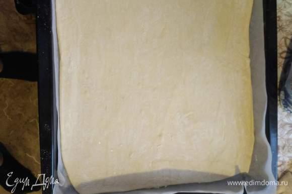 На противень кладем сначала лист пергамента, затем выкладываем раскатанное тесто.