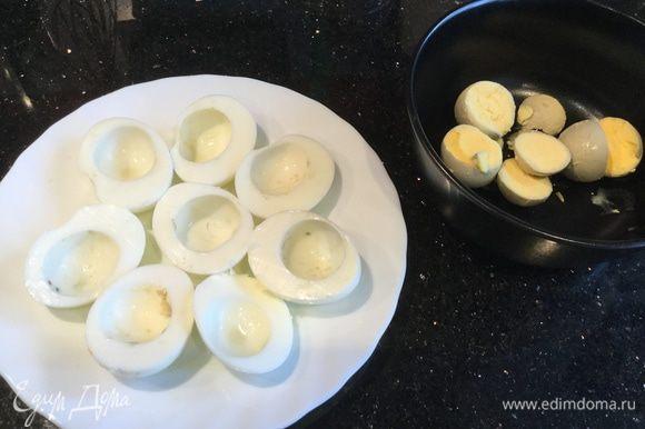 Яйца отварите вкрутую. Нарежьте на половинки, отделите белки от желтков.