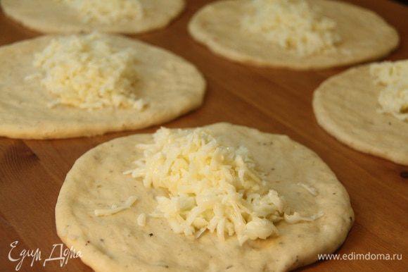Каждый кусок раскатать в лепешку диаметром примерно 12 — 15 см, выложить в центр начинку из сыра и белков.