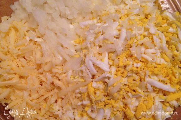 Приготовить начинку. Три яйца сварить вкрутую, очистить и натереть на крупной терке. Натереть сыр. Лук мелко порубить.