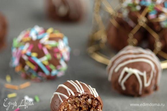 Готовые шарики я предлагаю заглазировать и украсить по желанию. На водяной бане топим любимый шоколад (у меня молочный), зубочисткой или, как делаю я, деревянной шпажкой — накалываем шарик и глазируем, излишки шоколада стряхиваем. Украшаем по желанию: у меня это разноцветные сахарные посыпки и белый шоколад. Готовые конфеты ставим в холодильник до застывания шоколада.