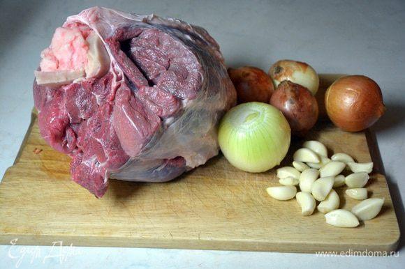Мясо помыть, лук почистить. Если лук чистый, то можно оставить с шелухой, она придаст золотистый цвет холодцу. Чеснок и морковь почистить. В пятилитровую кастрюлю выложить мясо, налить воду, вскипятить и подождать 5 минут. Слить воду и промыть мясо. Снова положить мясо в кастрюлю, добавить воду, чеснок, лук. Вскипятить и сразу убавить огонь, добавить соль. Бульон должен кипеть медленно, иначе он станет мутный.