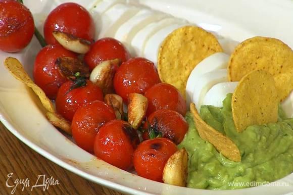 На блюдо выложить моцареллу, обжаренные помидоры с чесноком, гуакамоле и кукурузные чипсы.