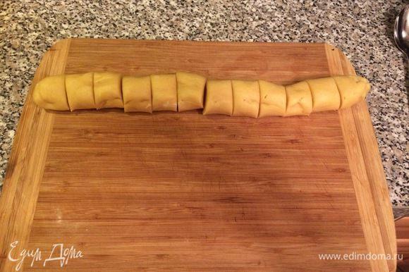 Через полчаса достаем из холодильника тесто, раскатаем из него колбаску и разрежем его на 12 равных частей.