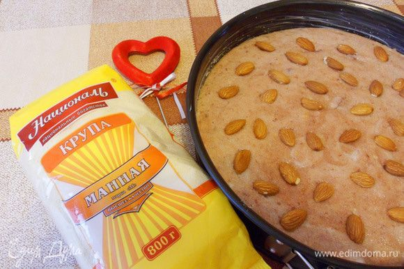 Форму для выпечки смазать маслом. выложить в нее тесто, посыпать оставшимися миндалем и сахаром. Духовку разогреть до 180°С.