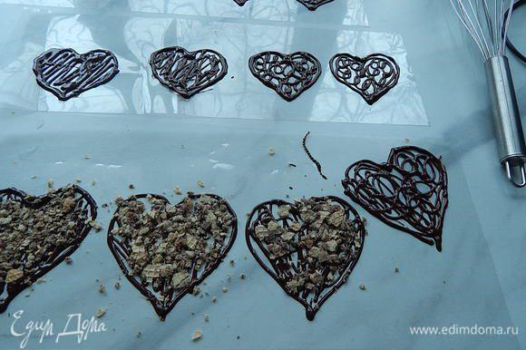 Пока еще шоколад не затвердел, сверху посыпать на одни сердечки обжаренные орехи, на другие раскрошить вафли, на следующие посыпать кофе, можно слегка придавить посыпку на шоколад. Оставшийся шоколад полить сверху посыпки. Оставить шоколадные заготовки хорошо затвердеть при комнатной температуре, на это уйдет примерно 25 — 35 минут.