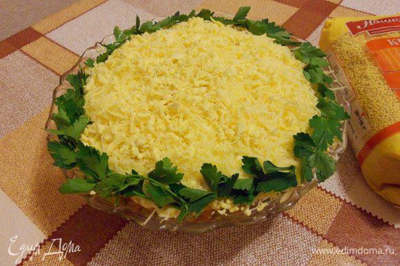 Сверху салат посыпать тертым сыром с раскрошенными желтками и украсить петрушкой.