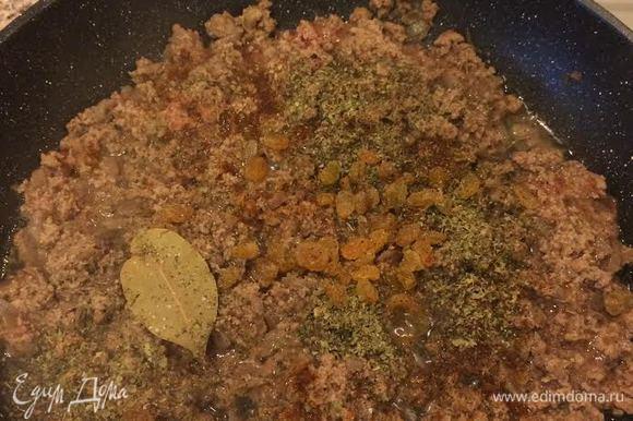 Затем добавить лавровый лист, паприку, соль, черный перец, майоран, изюм и перемешать.
