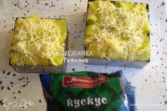 Сверху раскладываем кускус. Закрываем пироги верхней частью полосок цукини, присыпаем сыром. Ставим в разогретую до 180°С духовку на 10 — 15 минут до легкого зарумянивания.