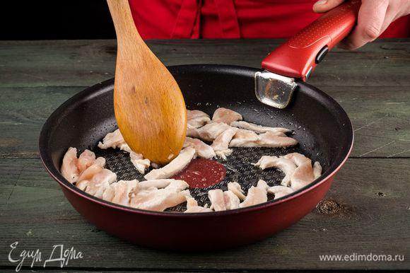 Куриное филе нарежьте соломкой и обжарьте на кунжутном масле до образования золотистой корочки.