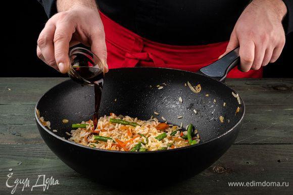 В вок добавляем соевый соус, немного обжариваем овощи в соусе и добавляем рис с паприкой.