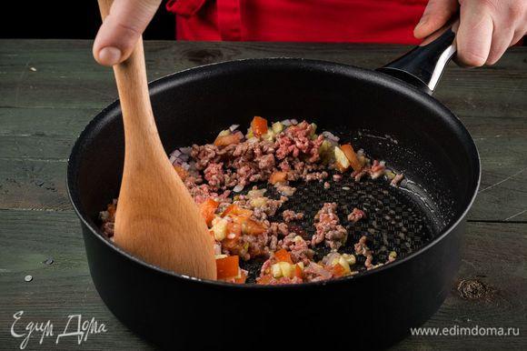 На небольшом количестве масла обжарить красный лук. Добавить фарш, лук шалот, чеснок и помидоры, тушить в течение 10 — 12 минут. Вся жидкость должна выпариться.