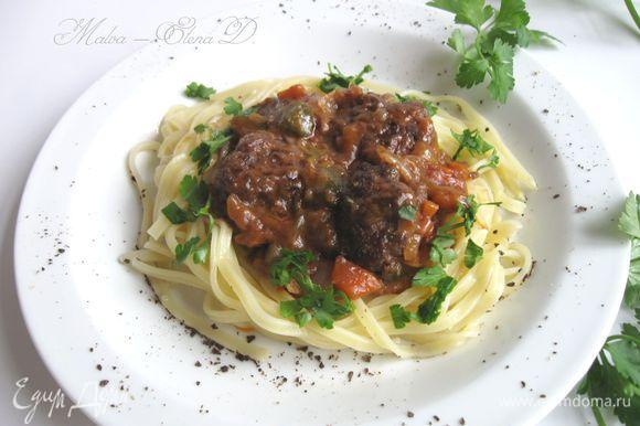 Сварить пасту аль денте, воду слить через дуршлаг. Петрушку измельчить. Подавать фрикадельки с соусом, пастой и петрушкой сразу после приготовления.