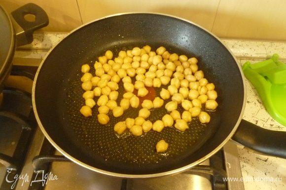 В сковороде разогреть 1 ст. л. масла, выложить нут и обжарить, помешивая, до золотистой корочки.