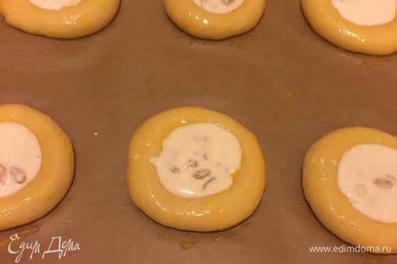В каждом колобке сделать углубление, бока смазать желтком, а в центр выложить крем.