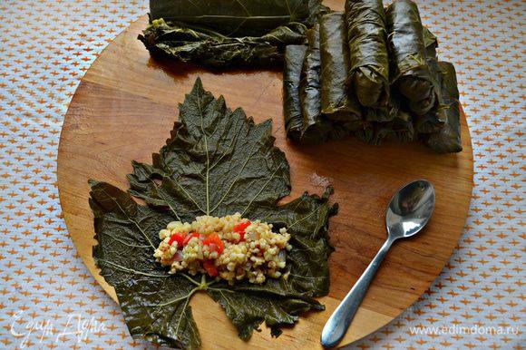 Виноградные листья разложите на ровной поверхности. На внутреннюю сторону каждого листа положите начинку и заверните трубочкой, по принципу формирования голубцов.