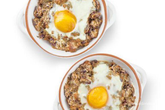Оставшимся маслом смажьте четыре небольшие формочки для запекания и присыпьте их остатками сухарей. В формочки выложите фасоль с сыром и поставьте в разогретую до 190°С духовку на 12–15 минут. Достаньте запеканку из духовки, в центр каждой формочки аккуратно разбейте яйцо так, чтобы желток остался целым. Верните запеканку в духовку на 7–8 минут. Яйца должны успеть схватиться, и подавайте.