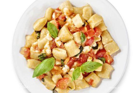Для соуса на сковороду с антипригарным покрытием налейте немного оливкового масла и обжарьте измельченный лук до мягкости. Выложите помидоры и жарьте их несколько минут. Как только из помидоров начнет выделяться сок, добавьте моцареллу, соль, сахар, порванный руками базилик и оливковое масло. Перемешайте соус и ньокки.