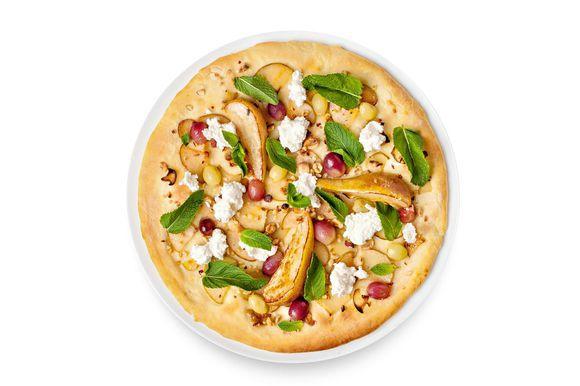 На готовую пиццу выложите карамелизованные груши, рикотту и листья мяты.