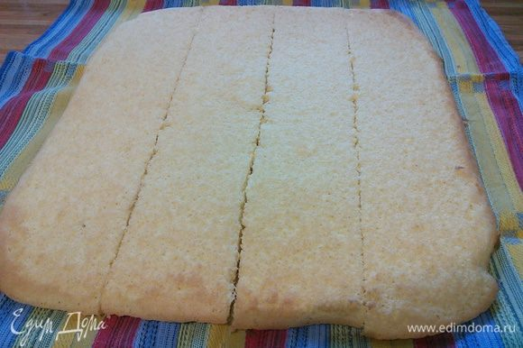 Бисквит выложить на полотенце, снять пергамент, остудить и разрезать на 4 полосы равной ширины.