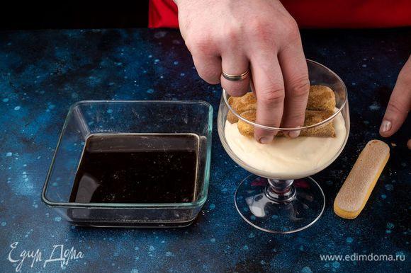 Затем выложите слой крема, снова добавьте пропитанный в кофе савоярди и слой крема.
