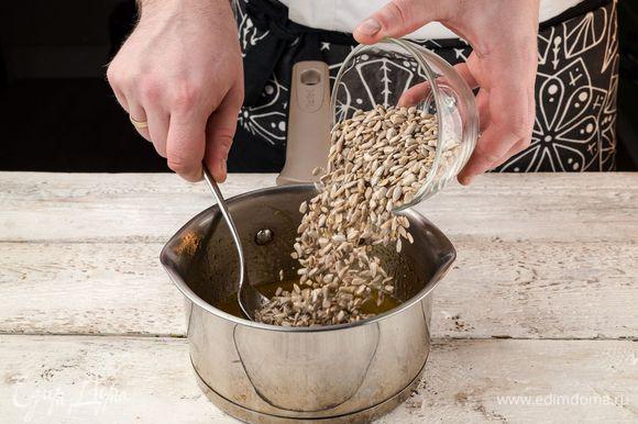 Когда сахар полностью растворится, а масса загустеет и потемнеет, снимите кастрюлю с огня. Добавьте в карамель очищенные семена подсолнечника. Тщательно перемешайте, чтобы карамель равномерно распределилась.