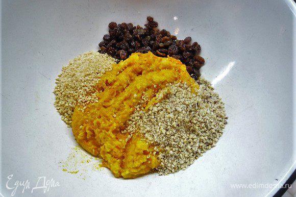 Выкладываем тыквенную массу в чашку, добавляем изюм, измельченные грецкие орехи, миндаль, цедру апельсина. Все хорошо перемешиваем.