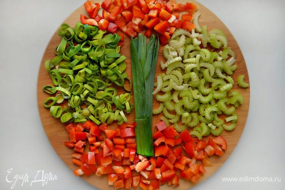 Овощи промыть, обсушить. Белую часть стебля лука-порея нарезать кольцами, сельдерей нарезать полукольцами, болгарский перец — небольшими кубиками.
