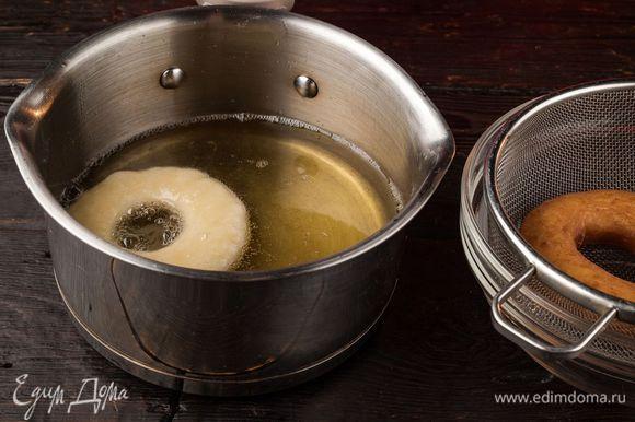 Налейте растительное масло в сотейник и выкладывайте в кипящее масло пончики. Положите готовые изделия на сито для стекания лишнего жира.