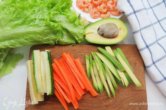 Подготавливаем овощную начинку. Авокадо, огурец и морковь нарезаем тонкими полосками. Листья салата моем и кладем обсушиться на полотенце.