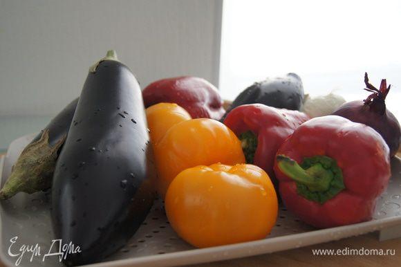 Разогреть духовку до 200°С. Подготовить овощи: помыть баклажаны, перцы, помидоры, лук. Шелуху с лука не снимать.
