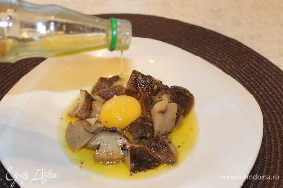 На теплую сервировочную тарелку положите грибы вместе с соусом, который получился в процессе приготовления. Отделите тщательно желток от белка так, чтобы желток остался целым, аккуратно положите его сверху на грибы. Посыпьте блюдо морской солью и полейте трюфельным маслом. Подавайте блюдо к столу.