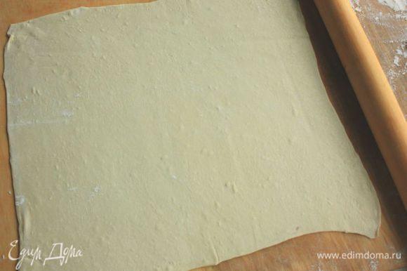 Прямоугольную форму (длиной 25 см, на 1,5 литра) выстлать пекарской бумагой. Слоеное тесто раскатать примерно 32 х 32 см и на скалке перенести в форму.