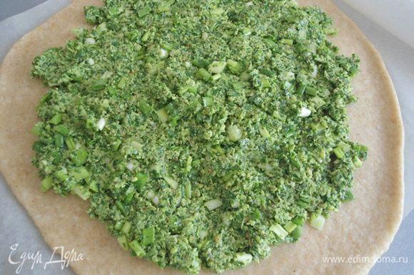 Тесто раскатать на бумаге для выпечки в круг. Зеленую и ароматную начинку распределить по тесту, оставляя края свободными.