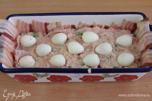 Выложить половину мясной начинки, уложить перепелиные яйца.
