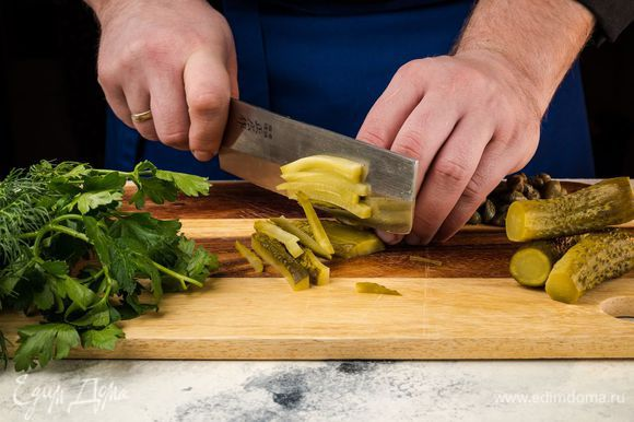 Приготовьте маринад. Огурцы мелко нарежьте, измельчите петрушку и укроп, крупно нарежьте каперсы.