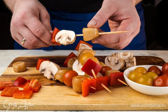 Помидоры черри, перец и грибы промойте. Перец нарежьте на квадраты. Если шампиньоны крупные, нарежьте их на четвертинки. Помидоры оставьте целыми, иначе быстро вытечет сок. На шпажки насадите, чередуя, морские гребешки, перец, грибы и помидоры. По желанию посыпьте овощи и грибы специями.