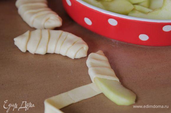 Яблоки очистить от кожуры, вырезать сердцевину, нарезать дольками. Обмотать каждую дольку полоской теста.