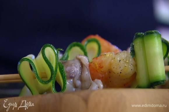 Кальмаров, креветок и сложенные в несколько раз гармошкой полоски цукини, чередуя, нанизать на шпажки, сбрызнуть оставшимся оливковым маслом и обжарить на разогретой сковороде-гриль со всех сторон до готовности.
